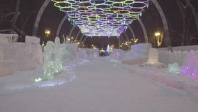 Winter night in the ice park. snow village. People and baby Walk In Ice Town During Snowfall. Children plays at the stock footage