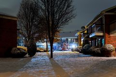 Winter night landscape - bench under winter trees and shining street lights with falling snowflakes. Winter night snow stock image