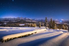 Winter night landscape. Starry blue night sky over winter mountains. Christmas night scenery in mountains. Winter night landscape. Starry blue night sky over royalty free stock photos
