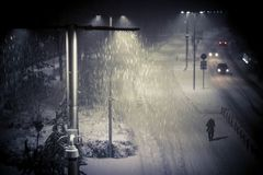 Winter night landscape, street with lanterns, a man walking along the road royalty free stock photography