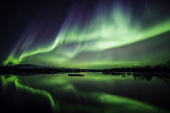 Winter Night. Northern lights blazing over lake Thingvellir national park in Iceland Royalty Free Stock Photography