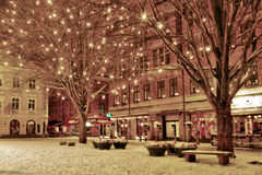 Winter night in the old city. With a bright shiny trees and snow on the ground and a TGIF restaurant with warm red lights at Lilla torg in malmo sweden royalty free stock images