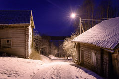 Winter night with old farm houses. Old farm houses along a road with a single streetlight during winter night Stock Photography