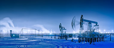 Winter night panoramic oil pumpjack. Royalty Free Stock Images