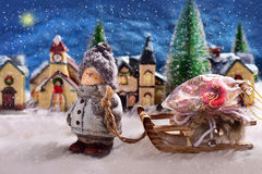 Winter night scene with a boy pulling a slad with christmas gift. Winter snowy night scene in small town with a boy pulling a sled with a bag of christmas stock image