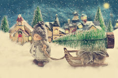 Winter night scene with a boy pulling a slad with christmas tree Royalty Free Stock Images