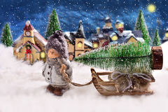 Winter night scene with a boy pulling a slad with christmas tree Royalty Free Stock Photos
