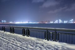 Winter night shot of embankment. Lot of snow on the ground and black metal fence stock image