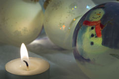Winter night. Snowman bauble warms by candle royalty free stock photo