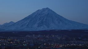 Winter night view of town scape - urban development on background cone of volcano. Winter night view of Kamchatka town scape - urban development of Petropavlovsk stock footage