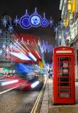 Winter nightscene in London on a decorated highstreet for christmas. Winter nightscene in London with a red telephone cell and blurred bus on a decorated Stock Images