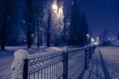 Winter nigt city in park with lantern lights royalty free stock photography