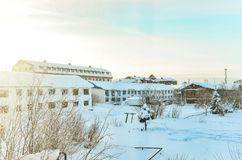 Winter in the Northern hinterland. On the background of barracks bright sun and frost stock image