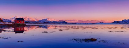 Winter Norway lake. Landscape with beautiful winter lake, red rorbu house and snowy mountains at sunset at Lofoten Islands in Northern Norway. Panoramic view royalty free stock images