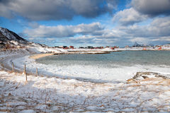 Winter Norway scenery : frozen beach of Sommaroy. Sommaroya, Troms county, Norway . Sandy beach covered by snow with small village in the background royalty free stock photo