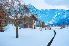 Winter in Obertraun, Salzkammergut, Austria. The narrow creek runs through the snowy garden in valley of Obertraun village, Salzkammergut, Austria stock photos