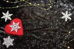 Winter- oder Weihnachtshintergrund oder Valentinsgrußkonzept mit weiße dekorative Schneeflocken und rotes Herz Stockfoto