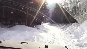 Winter off roading. Off road vehicle driving through a rough terrain covered with snow in the forest stock footage