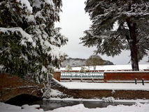 Winter in Old Amersham. Snow covered fir trees, old bridge, river Misbourne and   churchyard of St Mary`s Church surrounded by red brick wall with cast iron Stock Images