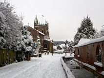 Winter in Old Amersham. Snow covered St Mary`s Church, trees, river Misbourne, red brick wall with cast iron railing, Old Amersham, Chilterns, Buckinghamshire Stock Photos