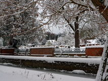 Winter in Old Amersham. Snow covered trees, river Misbourne and churchyard of St Mary`s Church surrounded by red brick wall with cast iron railings, Old Amersham Royalty Free Stock Images