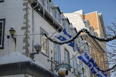 Winter in the Old City of Quebec. Snow-covered roofs and icicles in the Old City of Quebec. The flag of Quebec is blowing in the cold wind stock photo