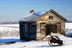 Winter at the Old Farm. Abandoned old shed in the winter with a piece of farm equipment out front stock photography