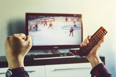 Winter Olympics final hockey game. A man watches the competition at home on TV. the fan is worried about his hockey team. Winter Olympics final hockey game stock images