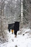 Winter outdoor leisure. Rock climbers with crash pads in a snowy forest,. Searching for a boulder rocks to climb. Extreem sport Stock Photo