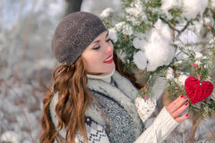 Winter outdoor portrait of a cute cheerful positive young girl with red heart decoration on a natural background Stock Images
