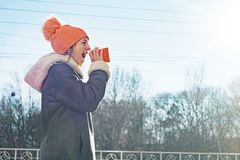 Winter outdoor portrait of young girl screaming in a megaphone paper cup, copy space royalty free stock photography