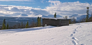 Winter panorama. From Lifttoppen, footprints on snow, trees, clouds and a shelter, V�l�dalen, Sweden Royalty Free Stock Images