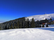 Winter panorama. Snowy slopes blue sky and mountain panorama Royalty Free Stock Photos