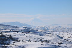 Winter panorama of Armenian mounatians with peak Ararat at the background. Fantastic winter panorama of the range of mountains with the peak of Ararat at the Royalty Free Stock Image