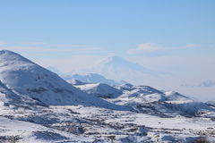 Winter panorama of Armenian mounatians with peak Ararat at the background. Fantastic winter panorama of the range of mountains with the peak of Ararat at the Royalty Free Stock Photos