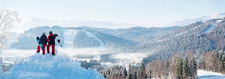Winter panorama of Carpathians mountains landscape and forests with snowboarders royalty free stock photography