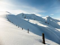 Winter panorama with fence posts and fresh powder of the ridge leading to the Hochwang peak near Chur. In the Swiss Alps Stock Image