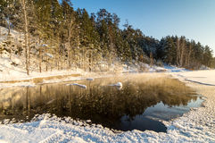 Winter panorama of frozen lake in a snowy forest with fog over the water, Russia, Royalty Free Stock Photo