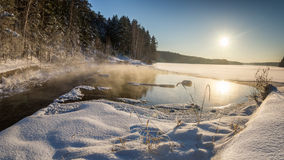 Winter panorama of frozen lake in a snowy forest with fog over the water, Russia, Stock Photos