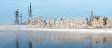 Winter panorama of Reftinskaya reservoir with power lines and a forest with reflection in the water, Russia, Ural Stock Photos