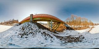 Winter panorama in the snow-covered forest near the bridge in nice sunny evening. Full spherical 360 by 180 degrees seamless royalty free stock image