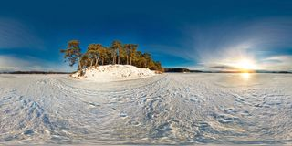 Winter panorama in the snow-covered forest near the river in nice sunny evening. Full spherical 360 by 180 degrees seamless royalty free stock image