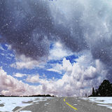 Winter panoramic landscape with road, silhouettes of trees, flying snow and clouds. White, gray and blue dramatic sky and highway with snow drifts. 3d rendering Royalty Free Stock Photos