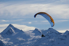 Winter paragliding over mountain peaks. Men paragliding in austrian alps over mountain peaks Stock Photography