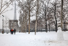 Winter in Paris. Paris,France- January 19, 2013: Winter image with a funny snowman and people walking to the Eiffel Tower on Champs de Mars after the first night Stock Photography