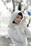 Winter in the park. Fashion portrait of a young pretty brunette wearing a white warm sweater with hood in winter forest Royalty Free Stock Photos