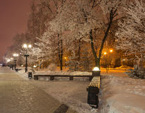 Winter park in the evening covered with snow. Winter park in the evening covered snow with a row of lamps Stock Photo