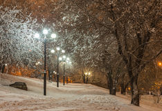 Winter park in the evening covered with snow. Winter park in the evening covered snow with a row of lamps Royalty Free Stock Photo