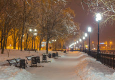 Winter park in the evening covered with snow. Winter park in the evening covered snow with a row of lamps Royalty Free Stock Images
