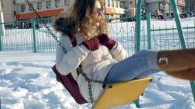 In winter park girl on a swing. 4k